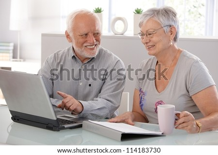 Senior people using laptop computer, smiling. - stock photo
