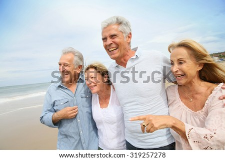 Senior people walking on the beach - stock photo