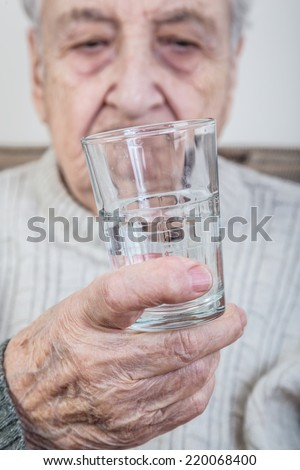 senior person holding a glass of water - stock photo