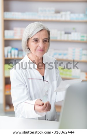 Senior pharmacist checking a prescription holding her glasses in one hand and script in the other as she reads information on the computer monitor