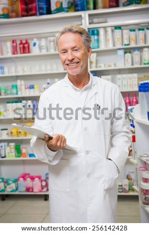 Senior pharmacist holding a clipboard in the pharmacy
