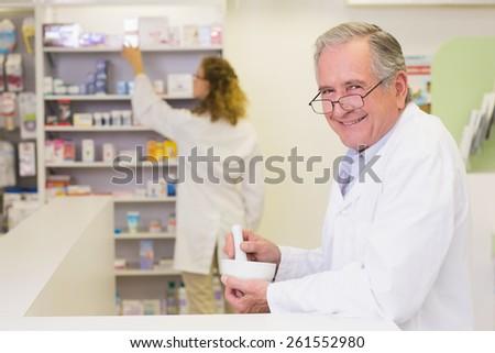Senior pharmacist mixing a medicine at the hospital pharmacy - stock photo