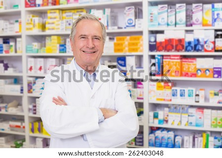 Senior pharmacist smiling at camera at the hospital pharmacy - stock photo