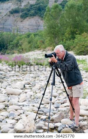 Senior photographer taking pictures of the beautiful nature of the Ardeche in France - stock photo