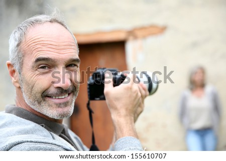 Senior photographer using digital camera