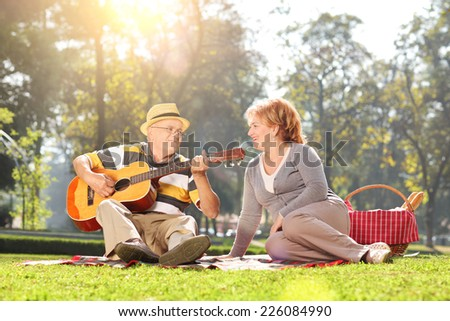 Senior playing guitar for his wife on a picnic in park  - stock photo