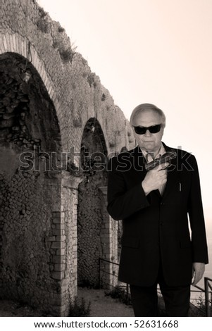 Senior police agent with a gun standing in historic italien ruins