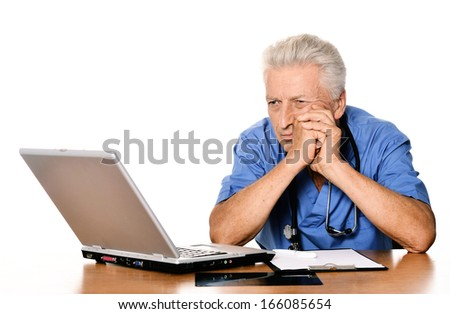 Senior positive doctor sitting at table with notebook. Isolated white background