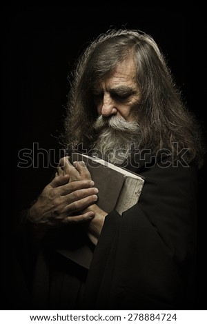 Senior Prayer, Old Man Praying with Hands on Bible Book, over Black Background - stock photo