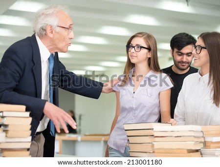 Senior professor giving lecture to young students at college campus - stock photo