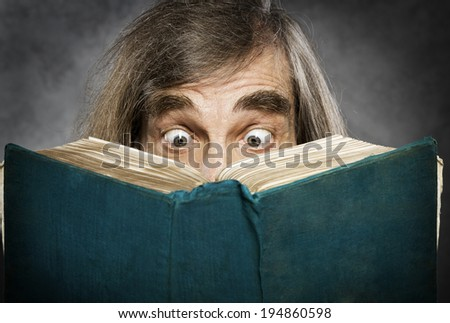 Senior reading open book, surprised old man, amazing eyes looking blank cover - stock photo