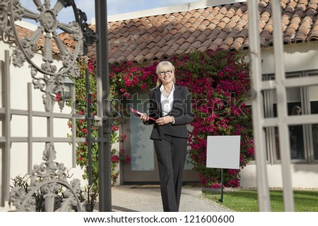 Senior real estate agent walking with clipboard - stock photo