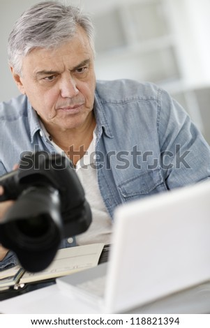 Senior reporter working in office in front of laptop - stock photo