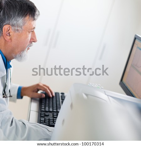 Senior researcher using a computer in the lab while working on an experiment (color toned image) - stock photo
