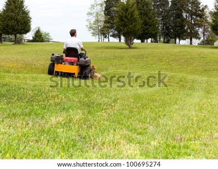 Senior retired male cutting the grass on expansive lawn using yellow zero-turn mower - stock photo