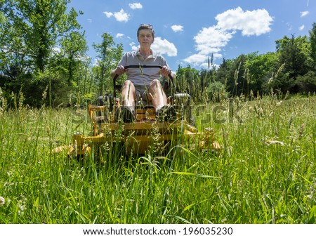 Senior retired male cutting very deep grass in a meadow or field after leaving it to grow for far too long before cutting using yellow zero-turn lawn mower - stock photo
