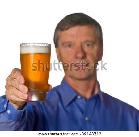 Senior retired male with a cool glass of beer with the man out of focus - stock photo