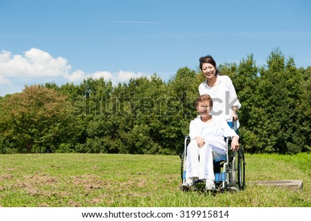 Senior riding in a wheelchair in the park - stock photo
