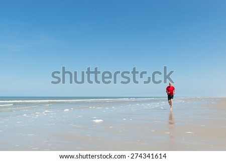 Senior runner at the beach - stock photo