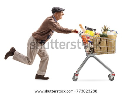 Senior running and pushing a shopping cart full of groceries isolated on white background