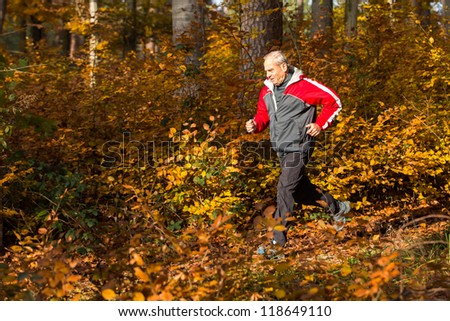 senior running through the forest - stock photo