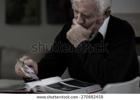 Senior sad man with photo missing his wife - stock photo