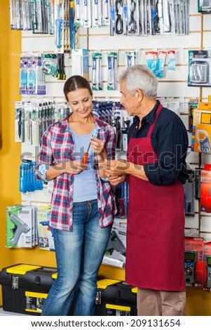 Senior salesman assisting female customer in buying screwdriver at hardware store - stock photo