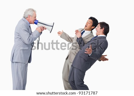 Senior salesman with megaphone yelling at his employees against a white background