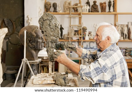 Senior sculptor making sculpture putting clay on wire skeleton sideview - stock photo