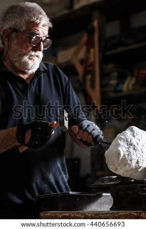 Senior sculptor working on his marble sculpture in his workshop with hammer and chisel.