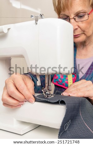 Senior seamstress woman working with clothing item on a sewing machine - stock photo