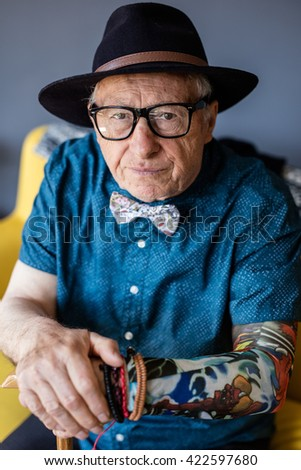 Senior serious man with tattoo holding his can and looking at the camera - stock photo