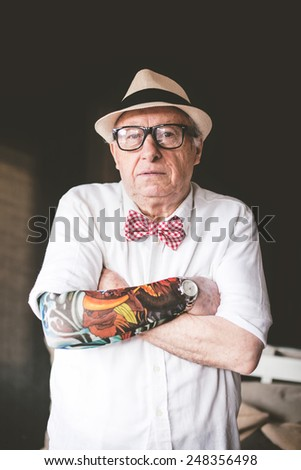 Senior serious man with tattoo looking at camera - stock photo