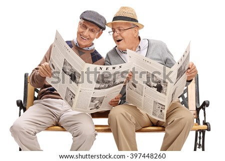 Senior showing something in the newspaper to his friend seated on a bench isolated on white background