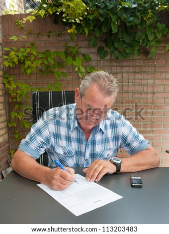 Senior signing a legal document and a mobile phone on table in his backyard