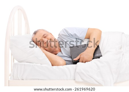 Senior sleeping in a bed covered with a blanket and holding a book isolated on white background - stock photo
