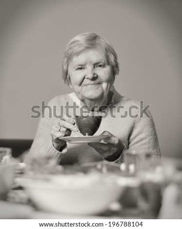 Senior smiling woman drinking tea. - stock photo