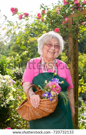 Senior smiling woman holding basket with flowers in garden