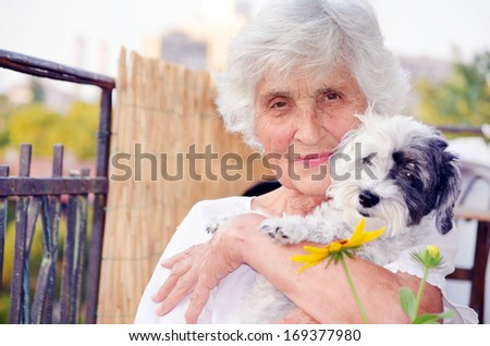 Senior smiling  woman hugging her  dog - stock photo