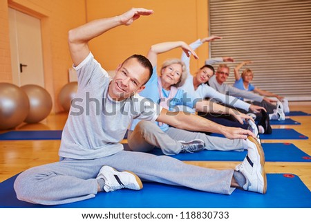 Senior sports class doing stretching exercises in a health club