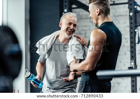 senior sportsman shaking hands with trainer in sport center