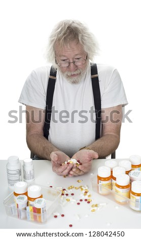 Senior staring down at prescriptions with a hanful of pills isolated on white - stock photo