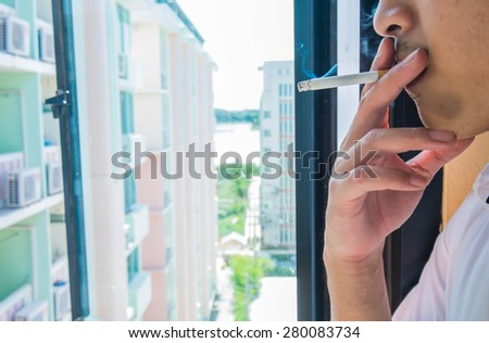 Senior student smoking for relaxing between class break at window with dormitory view - stock photo