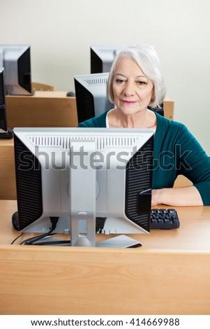 Senior Student Using Computer In Classroom - stock photo