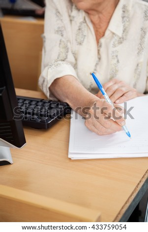 Senior Student Writing Notes In Computer Class - stock photo