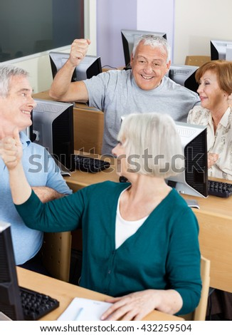 Senior Students Cheering In Computer Class - stock photo