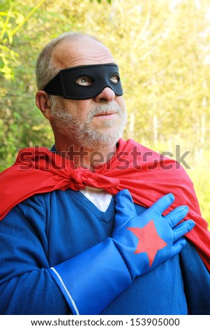Senior super hero having hands on heart and looking up