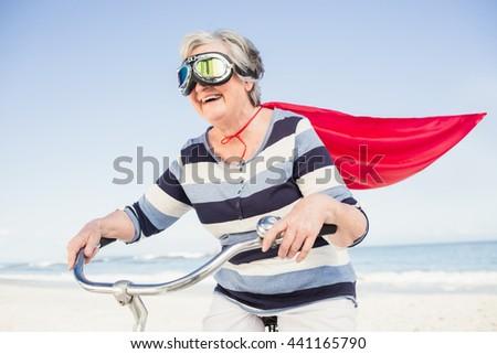 Senior superwoman on a bike on the beach - stock photo
