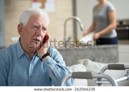 Senior talking on the phone and granddaughter washing dishes - stock photo