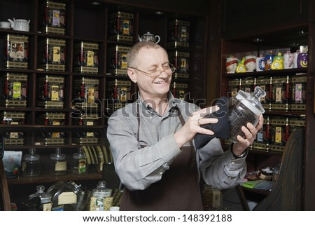 Senior tea shop owner dusting jar of tea - stock photo